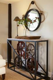 an industrial style table is paired with a hung mirror and