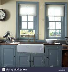 white blinds on windows above belfast sink in kitchen with pale