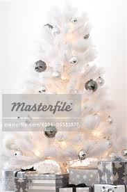 white tree decorated with silver ornaments and gifts