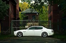 white maserati sedan maserati quattroporte white house street rain machine car building