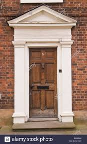 Frame Exterior Door Brown Wooden Front Door With White Frame And Pediment On Townhouse