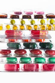 color tablets capsules and vitamins in blisters on the white