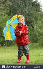 young boy with umbrella in a wet weather rain storm stock photo