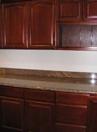 floating cherry oak kitchen cabinet on cream marble backsplash