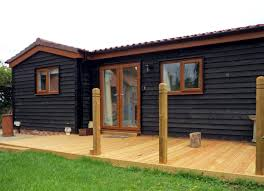 painted black timber exterior granny annexe with a large decked