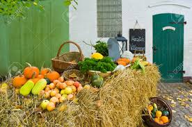 fruits and vegetables decorated on straw bales in front of a stock