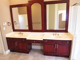 bathroom trough sink with wood vanity cabinets and mirror wood