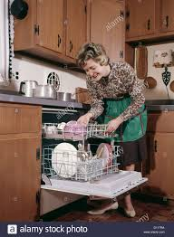 1960s smiling woman apron bending over emptying dishwasher in