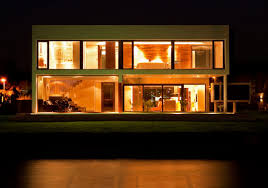 glasses door impressive modern house at night with green grass arround it also