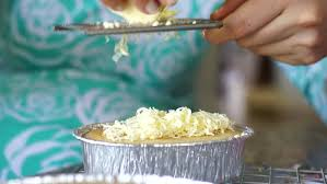 close up women are making cakes and grated cheddar cheese on the