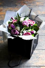 in gift grass covered box embellished with lavender roses pom poms and