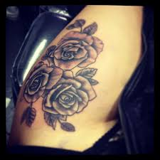 collection of 25 roses and pistol tattoos on side of thigh