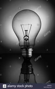 big clear light bulb standing in black and white stock photo