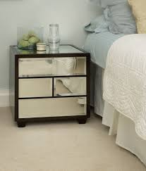white stained bed side table with three drawer and rounded white polished wooden bedside table in gray painted bedroom with