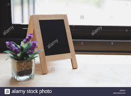 blank corkboard purple artificial flower in small glass pot on a