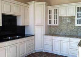 white kitchen cupboard with black tile and marble backsplash