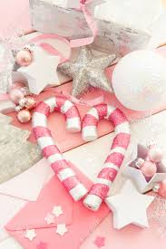 pink christmas decorations with glittery ornaments on striped