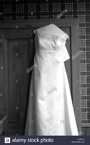 black and white image of wedding dress hanging on the door frame