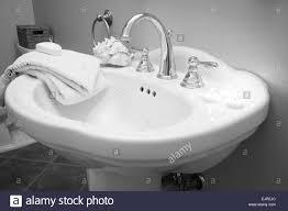 a beautiful bathroom sink with white shells candles and towels