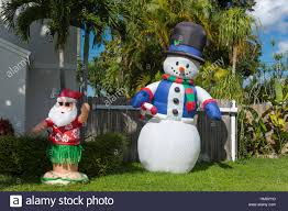 inflatable santa claus and snowman in front of palm trees in stock