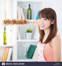 happy asian housewife with apron cleaning house hand holding a
