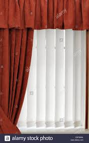 white vertical blinds with a red curtain england uk stock photo