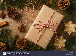 christmas present wrapped in kraft paper surrounded of decoration