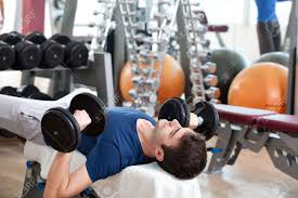 young man training in the gym chest dumbbell bench press stock