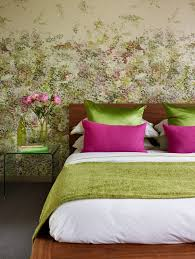 glass side tables for bedroom floral wallpaper and satin green pillows for spring styled bedroom