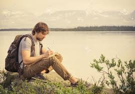 outdoor traveler images Young man traveler with backpack reading book and writing notes jpg