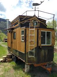 custom tiny house features hobbit door to a balcony curbed
