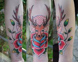 traditional deer head in rose tattoo on arm