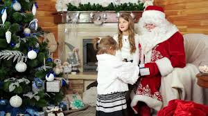 little girls visit santa at his residence happy sister sitting on