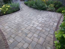 square brick stone patio floor with green garden and side walk of