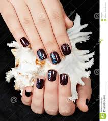hands with short manicured nails colored with dark purple nail