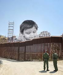 a child peers over the us mexico border wall in a giant new