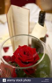 red roses in glass bowl menu and bottle of wine set on a table at