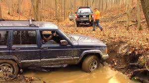 mud jeep cherokee jeep cherokee challenges toyota land crusier on mud gets damaged