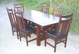 inlaid dining table and chairs shown without leaves surrounded by six inlaid dining chairs