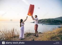 Photography Lovers Couple In Love At Sunset Releasing A Lantern For Good Luck