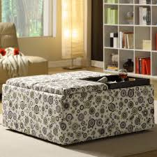 square fabric ottoman with circles pattern plus black tray placed