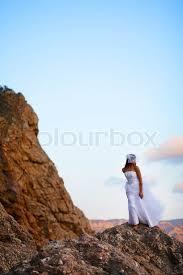 bride in fashion wedding dress posing on mountain over sea stock