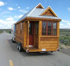 tiny house for sale on wheels which is being moved is moved by car