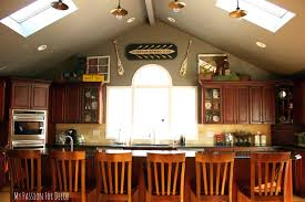 What To Put Above Kitchen Cabinets by Decorating Above Kitchen Cabinets With Vaulted Ceilin