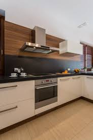 cream wooden kitchen cabinets brown wooden wall cream wall with furniture cream wall and white ceiling with chandelier and downlight white wooden kitchen cabinets brown wooden