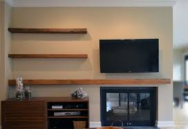 wall mounted tv and barn wood floating shelves over fireplace also