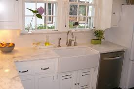 white porcelain sink installed in the kitchen with white cabinets