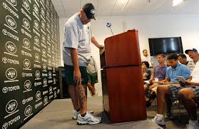 Jets Coach Rex Ryan show off his new tatoo to the press.