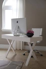 beautiful office with a sleek white x base lacquer desk and faux leather chrome desk chair taupe walls with light crisp cotton curtains