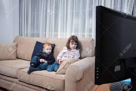 sur canapé deux enfants assis sur canapé à regarder la télévision banque d